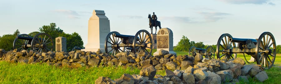 Cannons and monuments beside a rock wall at the Gettysburg Battlefield in Pennsylvania