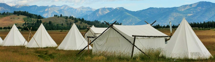Several tents in a grassy field near mountains
