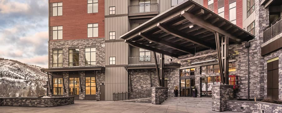Wyndham Resort at Avon stands beside a snowy mountain, with an overhang by the front door