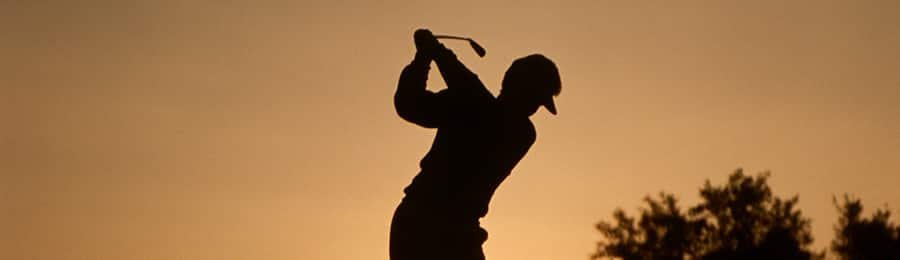 The silhouette of a man golfing at dusk