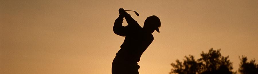 夕暮れ時にゴルフを楽しむ男性のシルエット