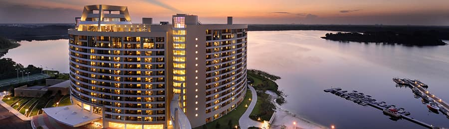 An illuminated Bay Lake Tower at dusk overlooking Bay Lake