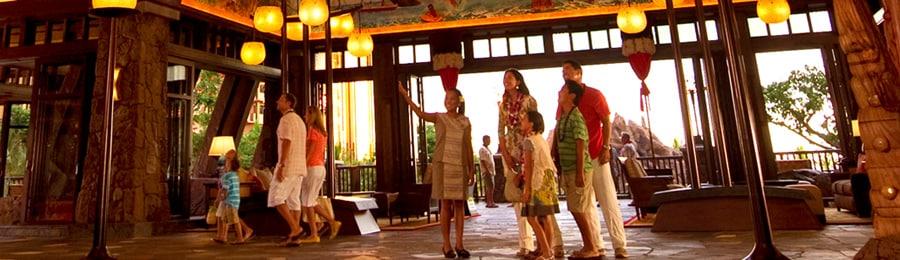Two families admire the Hawaiian-themed lobby at Aulani, A Disney Resort & Spa