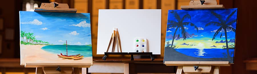 2 paintings on easels beside a blank canvas