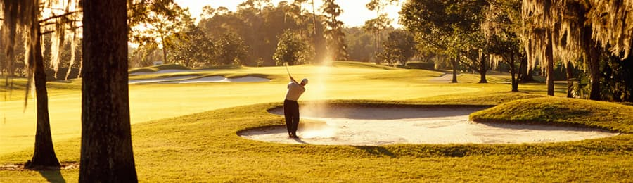 A golfer playing a ball out of the sand trap