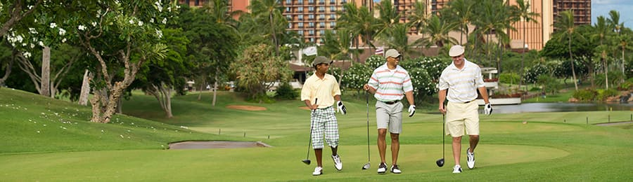 3 men wearing shorts and caps walk down a lush golf course in front of a large hotel
