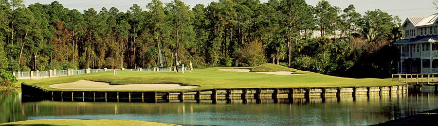 Four golfers on a golf course beside a large water hazard