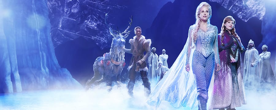 Actors portraying Elsa, Anna and Kristoff stand on the stage of Frozen with other members of the company
