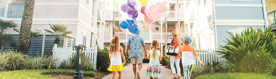 A family of 5 carrying balloons while walking into a Disney Vacation Club Resort