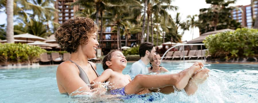 A boy laughs as a woman picks him up in a large pool surrounded by palm trees