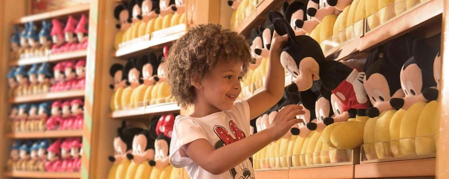 A smiling young girl picks up a Mickey Mouse plush from a 4 tiered wall of Mickey Mouse plushes