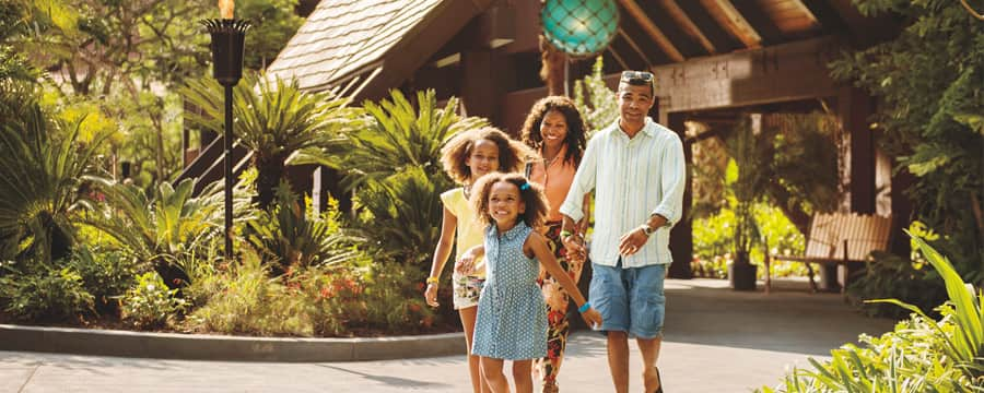 A family walking near the entrance to Disney's Polynesian Village Resort in Florida