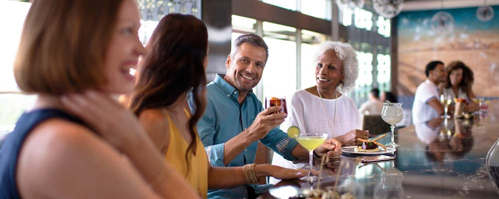A man holding a drink sits at a bar with several women, all with drinks and appetizers in front of them