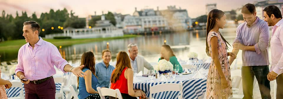 Attendees at a catered event by the water that includes dining tables with elegant floral displays
