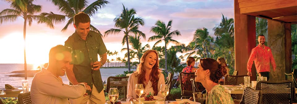 Guests enjoy a patio meal and the sunset at Aulani Resort