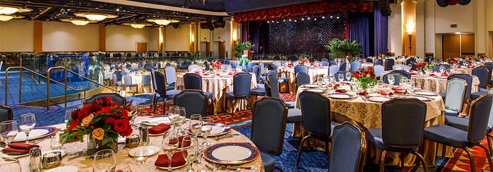 A ballroom with round tables, chairs, and a stage