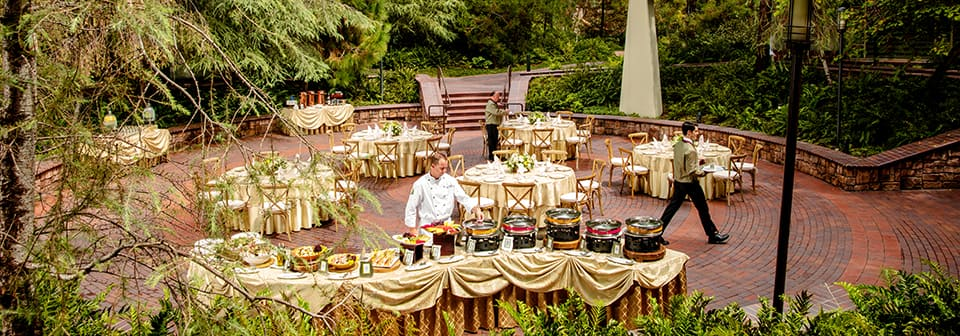 An outdoor event set up with elegant dining tables, floral displays and a buffet