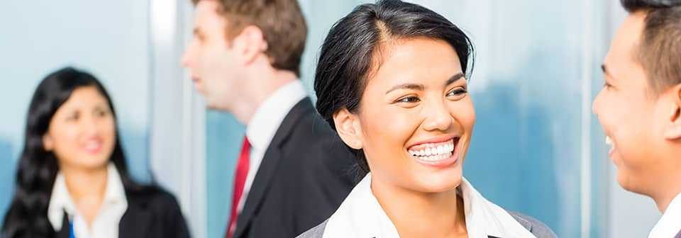 A woman in the foreground wears business attire and a smile, as a man and woman, also in business attire, talk in the background