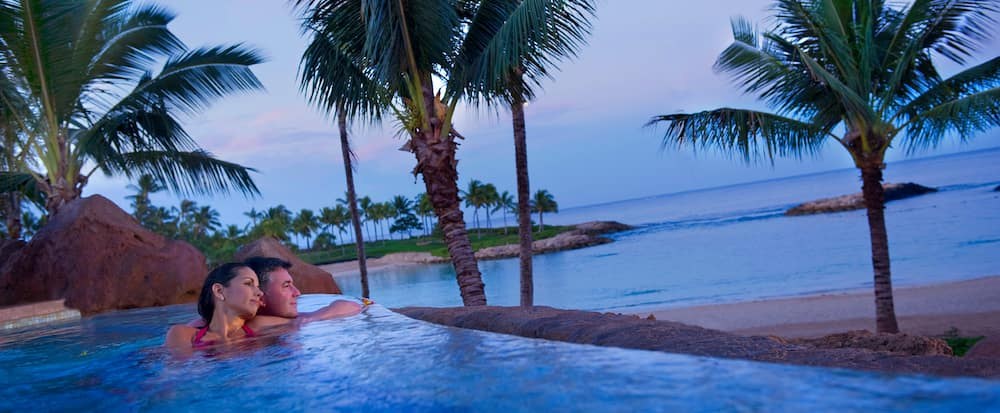 With the beachfront in the background, a couple lounges together in the  adults only whirlpool