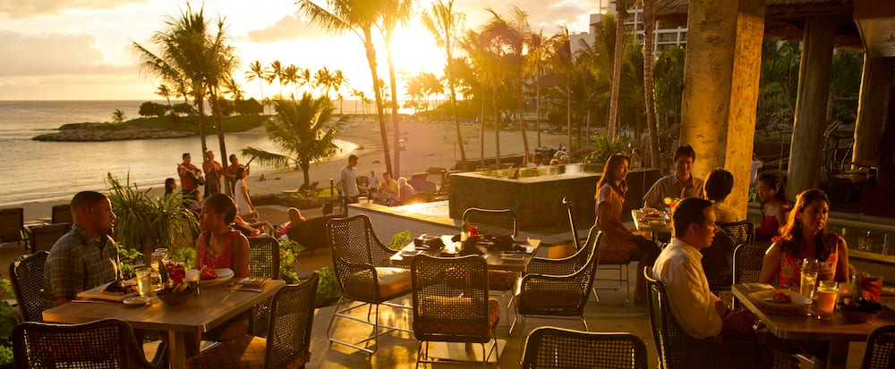 Two couples and a party of 4 dine on an outdoor patio with palm trees and ocean views as the sun sets