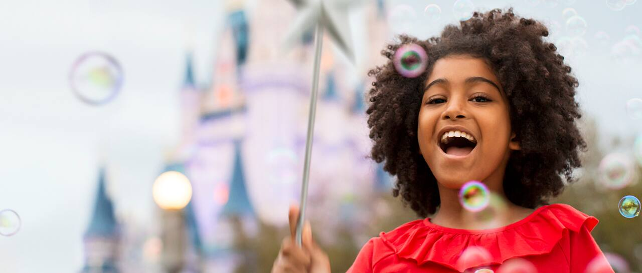 Outside a castle, a girl holds a wand and laughs as bubbles fill the air
