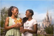 A woman holding a Mickey Mouse pretzel smiles with a young girl in front of Cinderella Castle