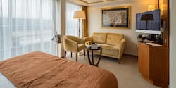 A Category AP room, featuring a double bed, a club chair and loveseat, and a large sliding glass door to a balcony.