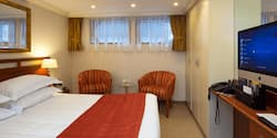 A Category D room, featuring a double bed, two club chairs and a table.