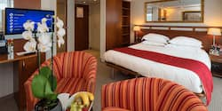 A Category Suite room, featuring a double bed, 2 club chairs and a desk.