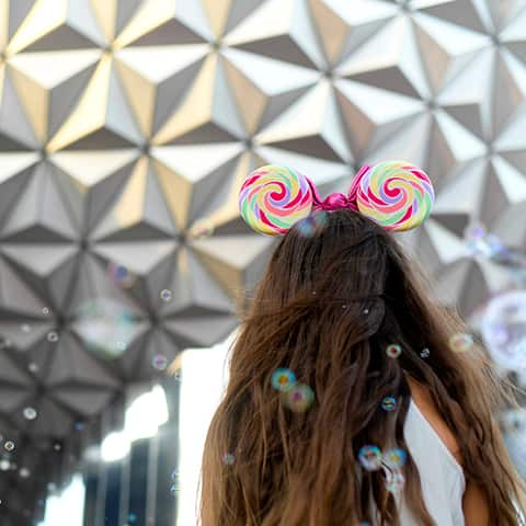The back of a woman with long hair wearing a Minnie Mouse ear headband with swirls, stands in front of Spaceship Earth at Epcot