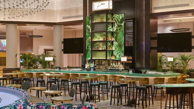 Phins lounge area, featuring a large curving bar surrounded by stools and several tables with stools nearby.