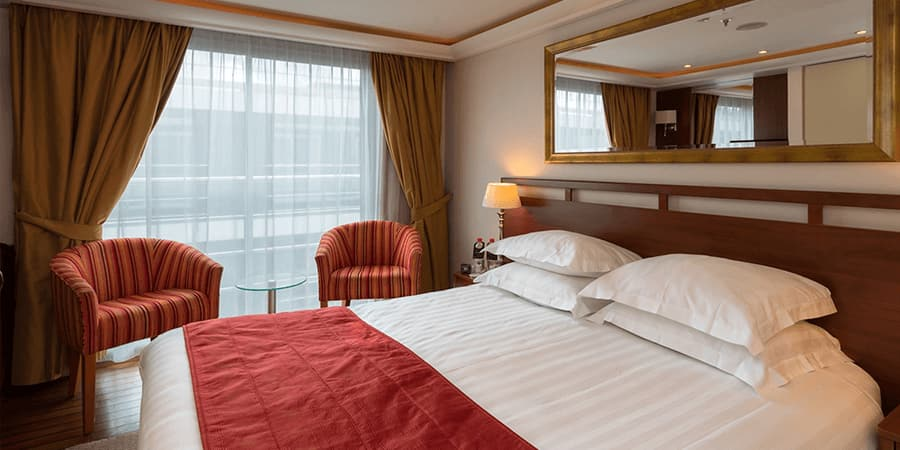 A Category B room, featuring a double bed, two club chairs and a large sliding glass door to a balcony.