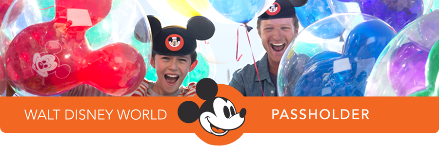 A father and son wearing Mickey ears smile while surrounded by helium balloons