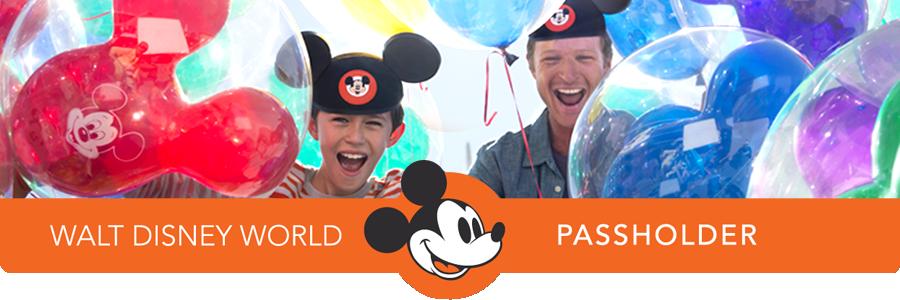 Un padre y su hijo con orejas de Mickey sonríen rodeados de globos de helio