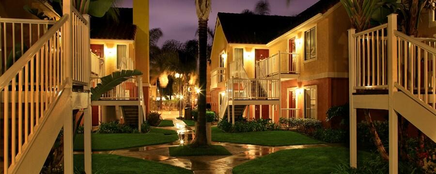 Una palmera situada en un patio entre dos edificios de dos niveles, encendidos de noche